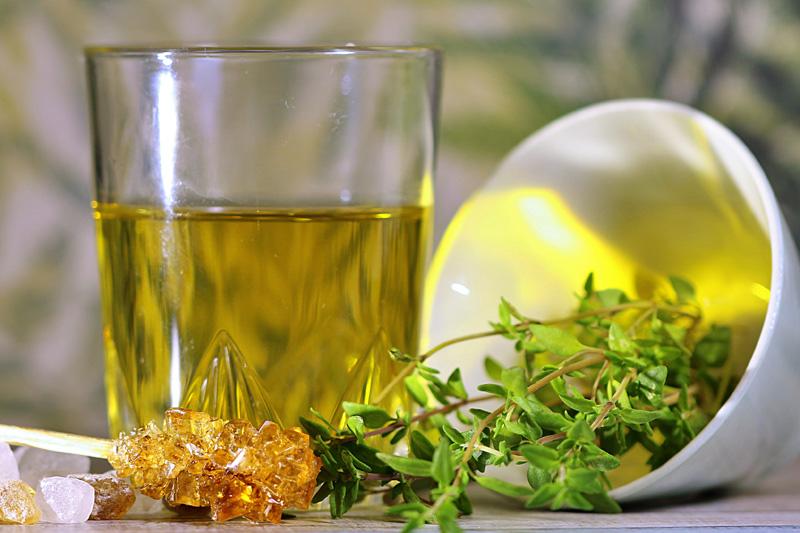 Glas Thymiantee mit Thymianzweig und Zuckerlöffel