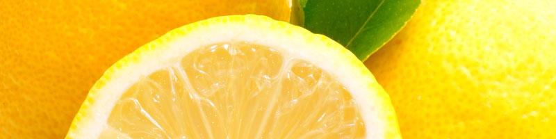 Zitronenscheibe vor ganzen Zitronen