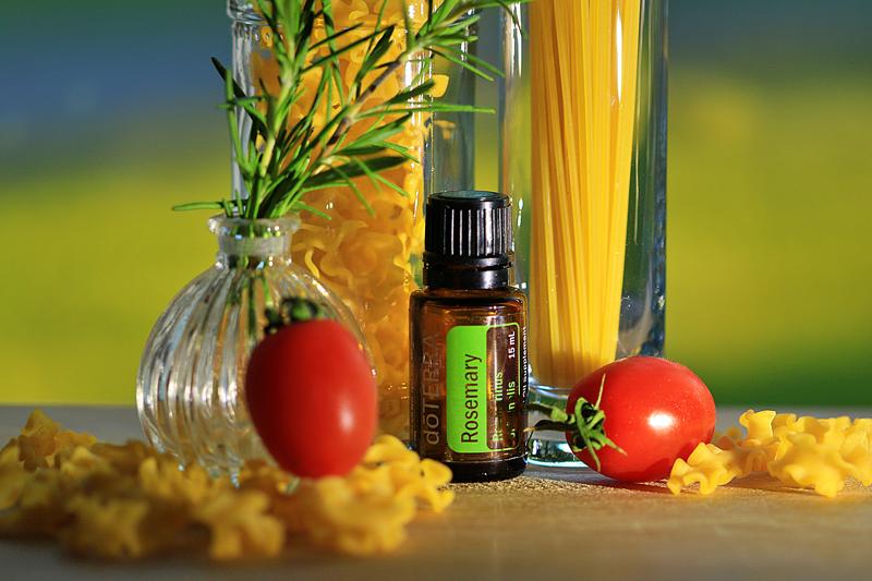 Tomaten, Nudeln, Rosmarinzweig - dazwischen ein Fläschchen Rosmarinöl