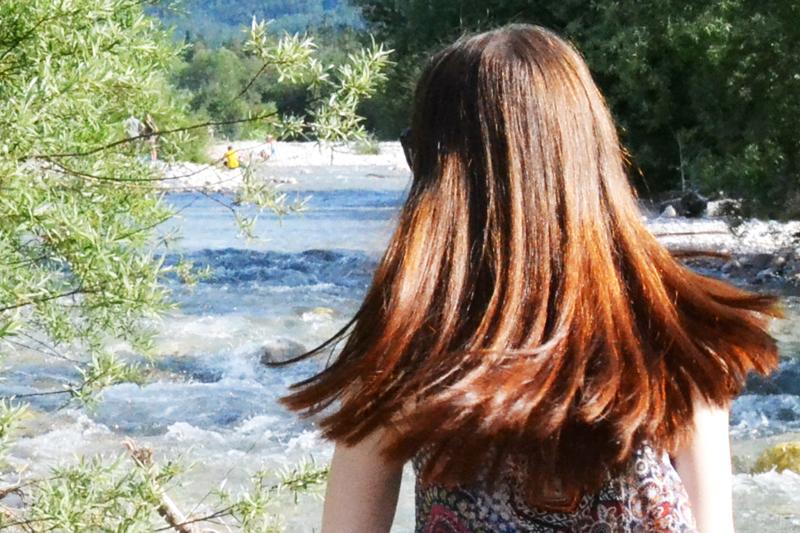 lange rote Haare glänzen in der Sonne, Hintergrund Bach un dBäume