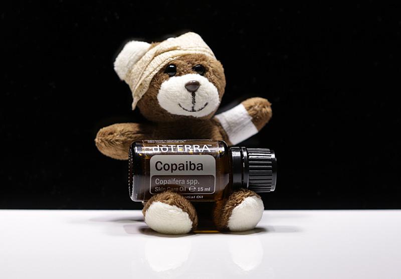 Teddybär mit verbundenem Arm und Kopf hält ein Copaiba Öl-Fläschchen