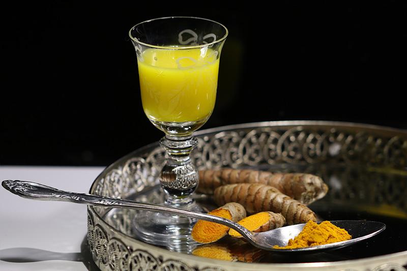 Glas mit Kurkumagetränk, davor Tablett mit Pulver und Wurzeln