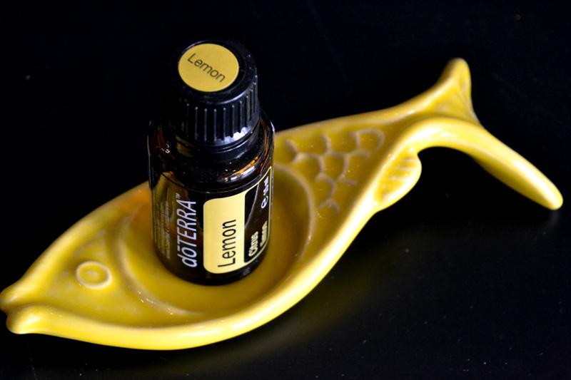 Lemon-Ölfläschchen auf gelbem Keramikfisch