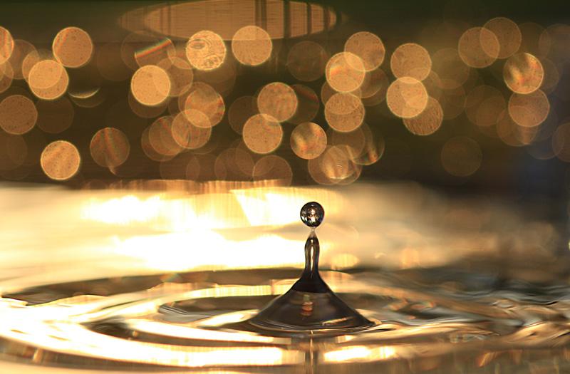 aufspringender Wassertropfen in gelbgoldenem Licht
