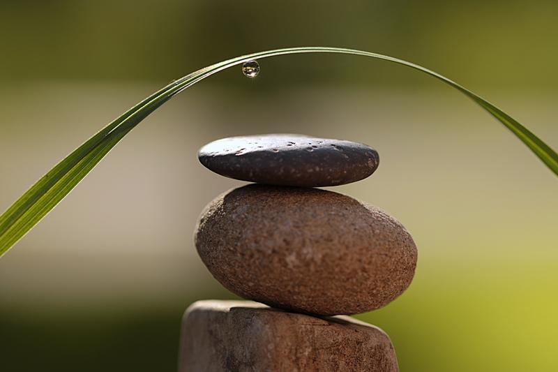 Steine in Balance übereinandergestapelt, darüber Grashalm