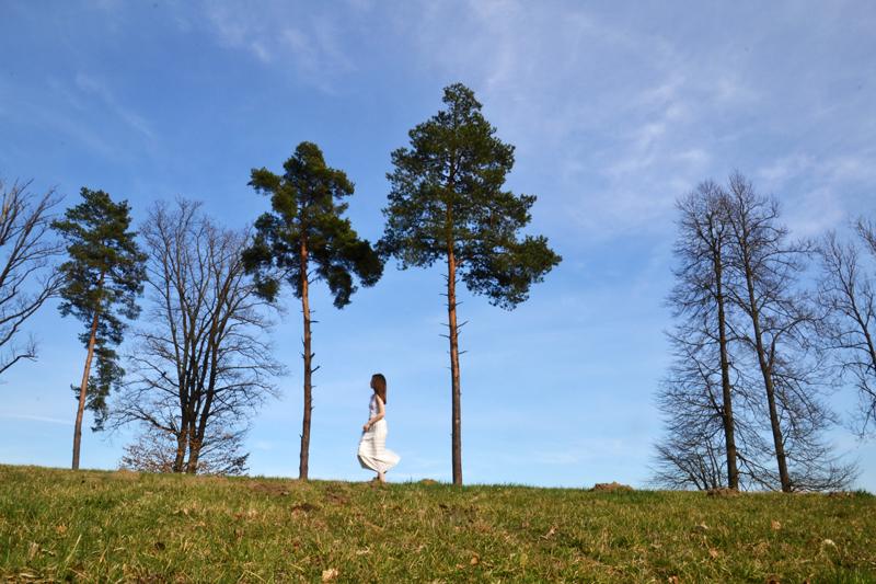 Junge Frau in weißem Kleid spaziert zwischen Bäumen