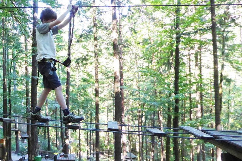 Kind balanciert über hängende Bretter in Kletterpark