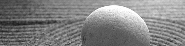 runder Stein im Vordergrund, Sand mit Muster im Hintergrund