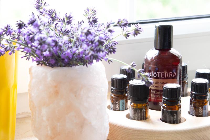 links vorne ist Lavendel in einer Vase, rechts im Hintergrund sind Ölfläschchen