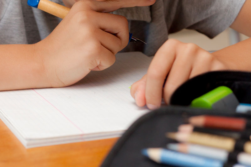 Zwei Kinderhände mit Stift über weißem Blatt Papier