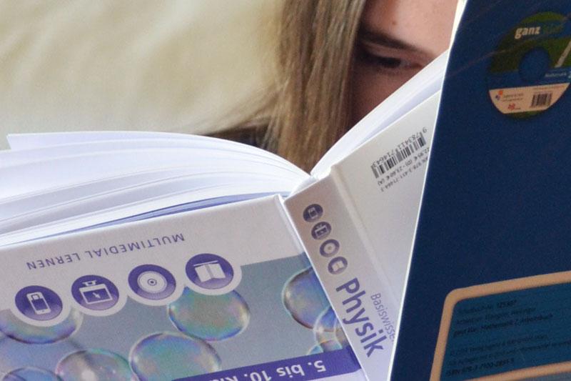 In Schulbücher lesende Schülerin