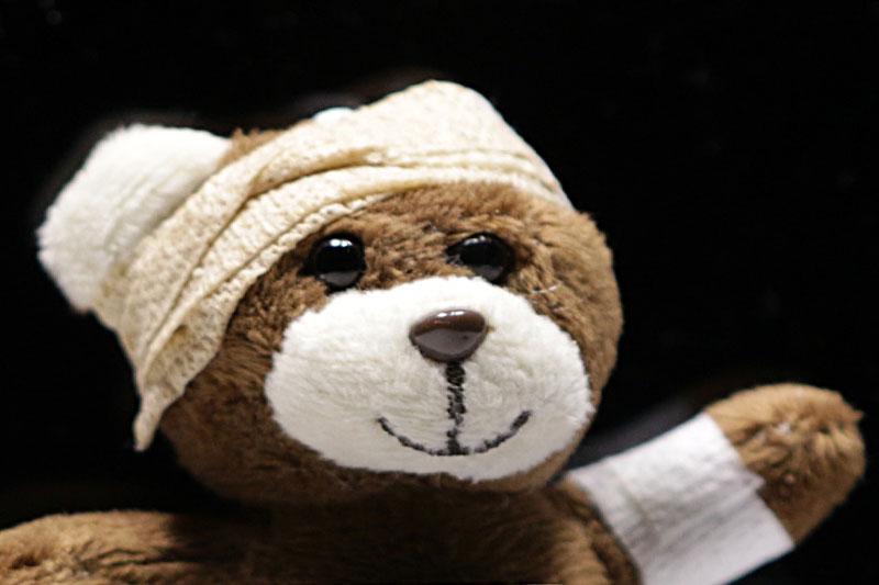 Teddy mit verbundenem Kopf und verbundener Hand