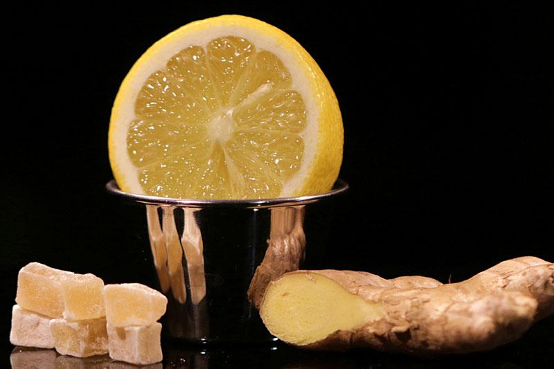 Ingwerwurzel neben Schale mit Zitronenscheibe und kandiertem Ingwer