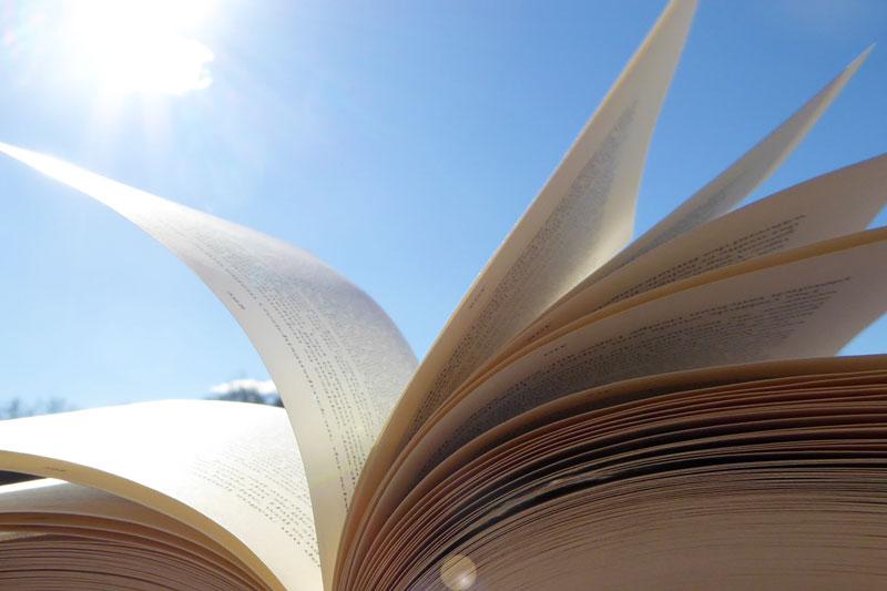 aufgeschlagenes Buch vor blauem Himmel