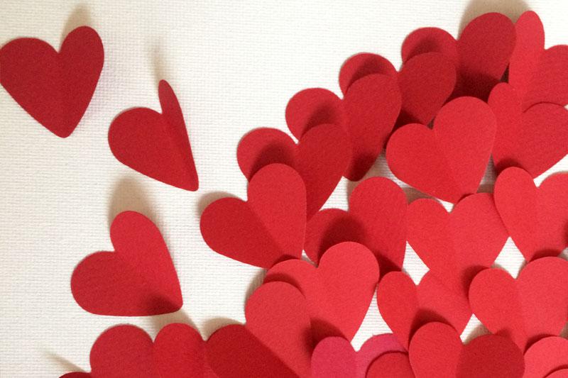 aus rotem Papier ausgeschnittene Herzen auf Leinwand