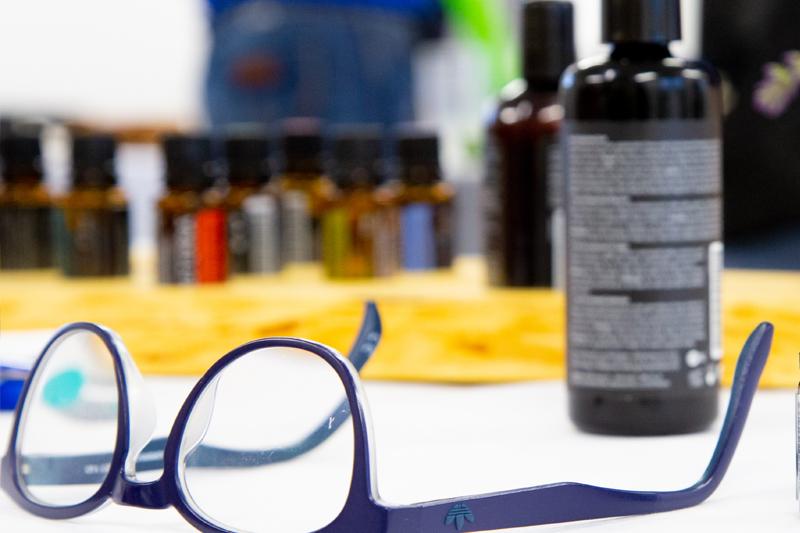 Brille vor unscharf abgebildetem Basisöl und kleinen Öl-Fläschchen