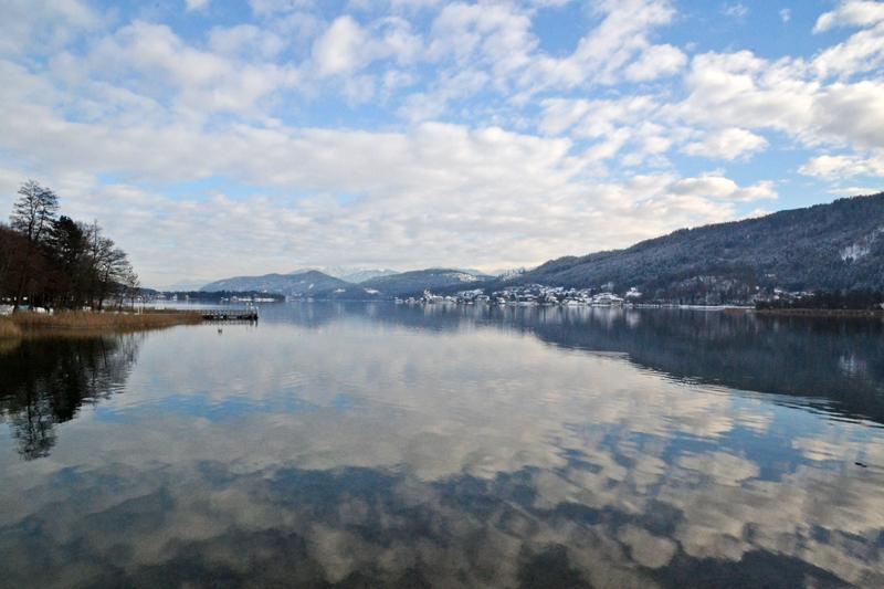 Die Wolken und der blaue Himmel spiegeln sich im Wasser des Sees