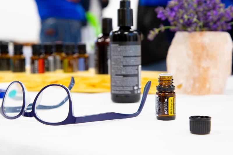Brille im Vordergrund, hinten Trägerölflache, diverse Flaschen von ätherischen Ölen und eine Salzsteinvase mit Lavendel