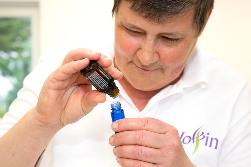 Ingrid tropft ein ätherisches Öl in ein kleines RollOn-Fläschchen