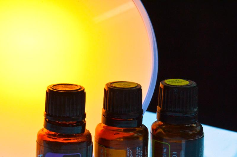 Drei Ölfläschen vor stimmungsvoller Lichtquelle