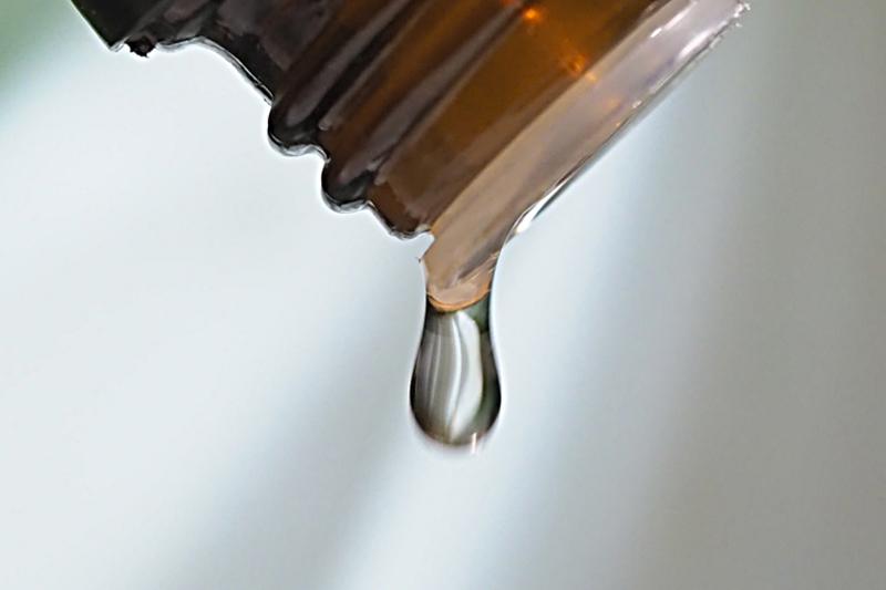 Tröpfchen rinnt aus eine Aromaöl-Flasche